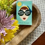 flowers in a wooden bowl with paperback book