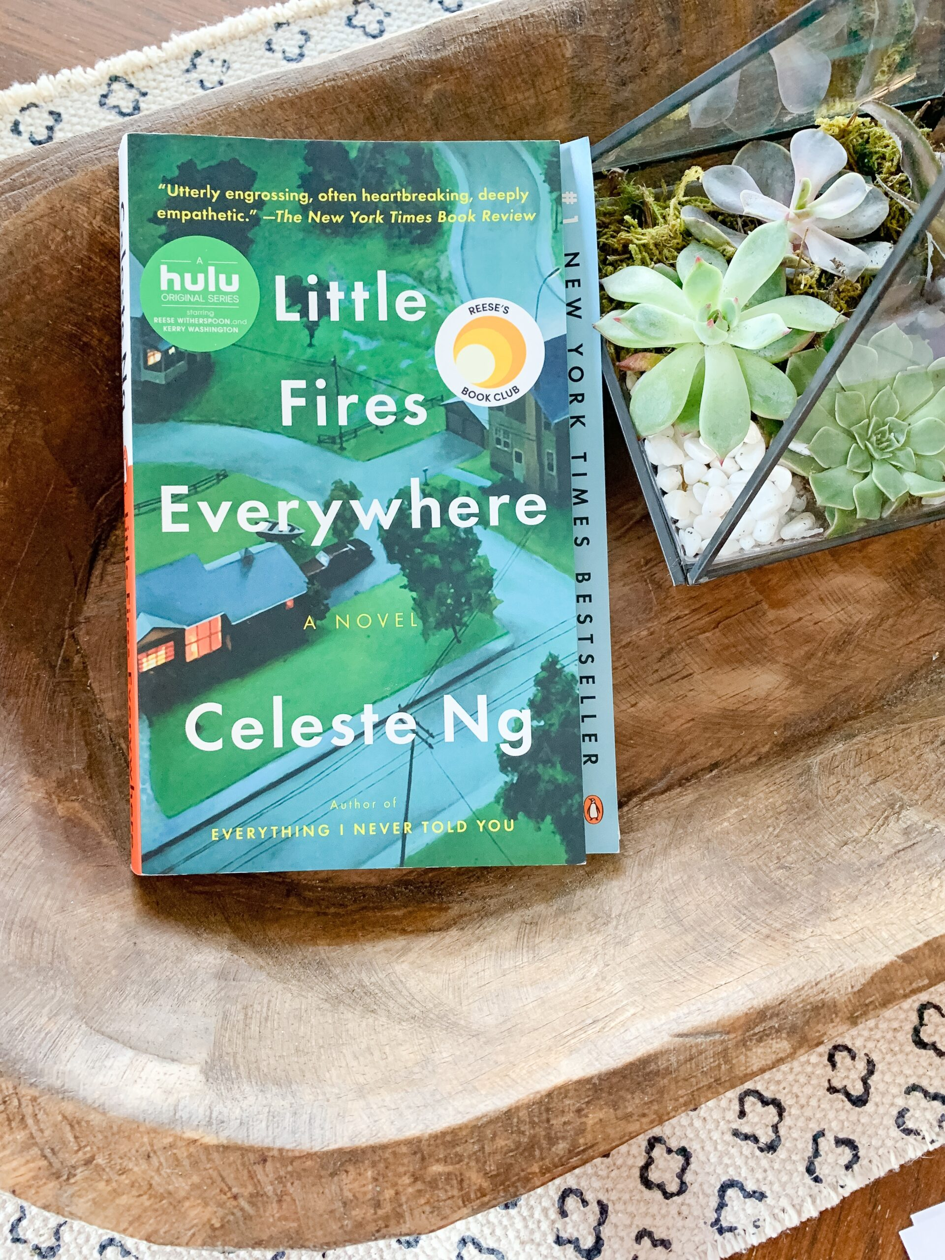 Little Fires Everywhere book in wooden bowl with succulents