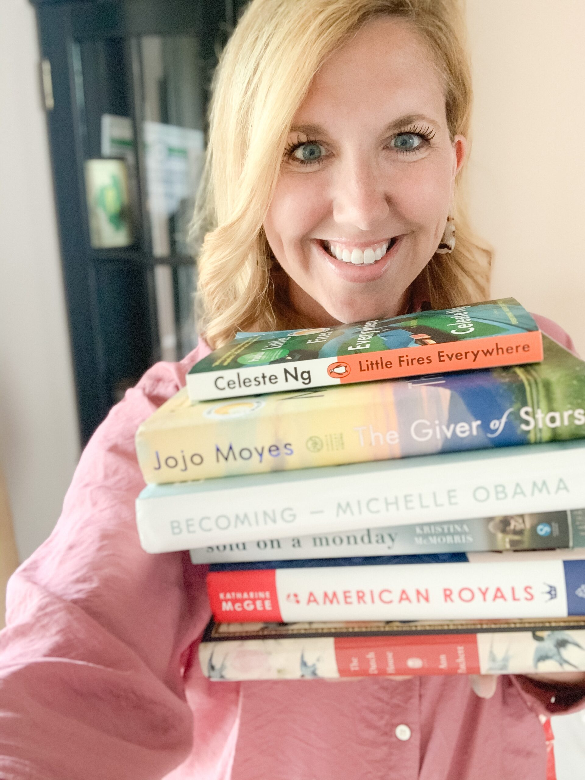 blonde woman with stack of popular books for book-a-month reading challenge