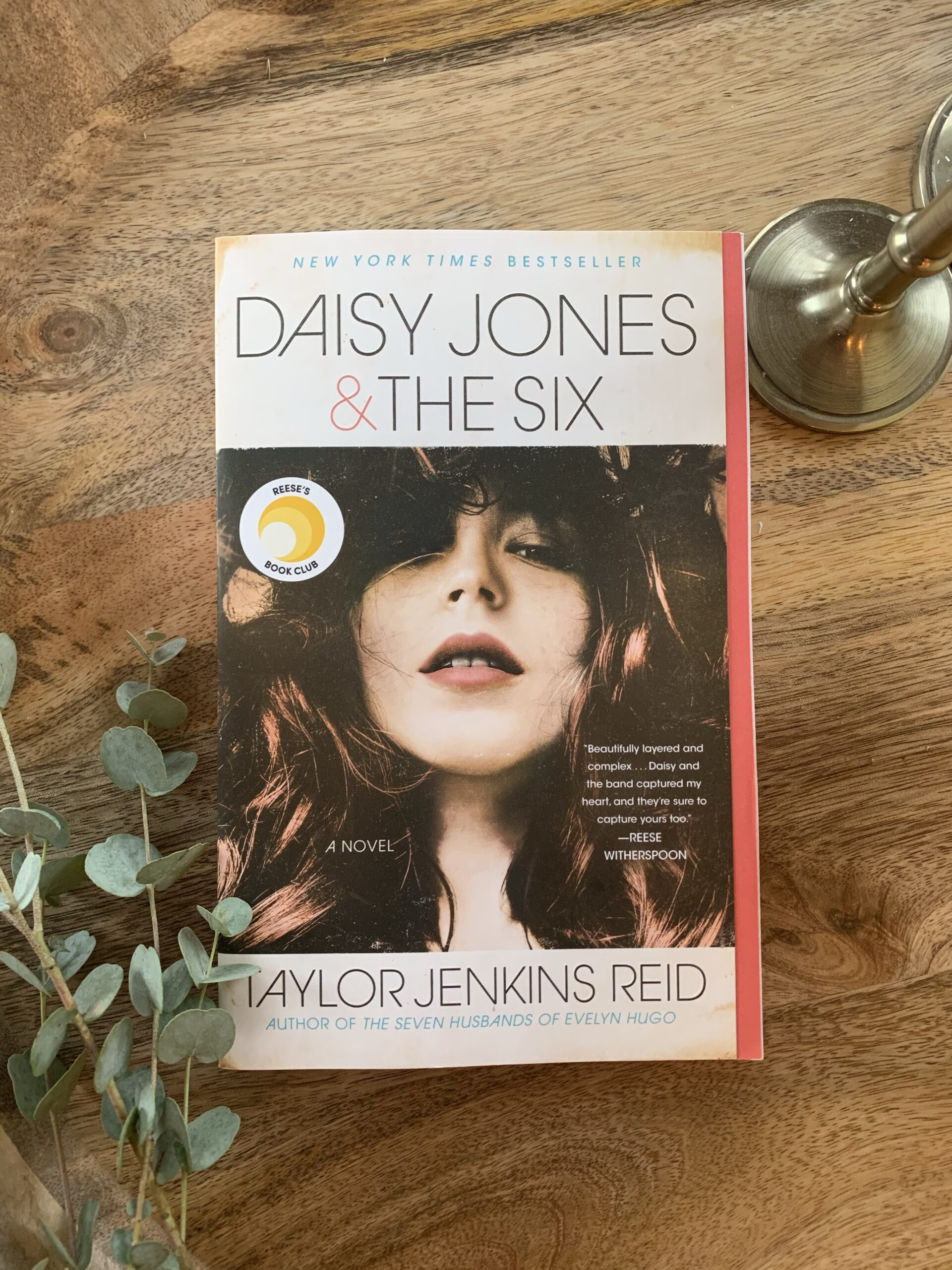 Image of the novel Daisy Jones and the Six, a novel by Taylor Jenkins Reid. Book with image of rock star sits on a wooden tray.