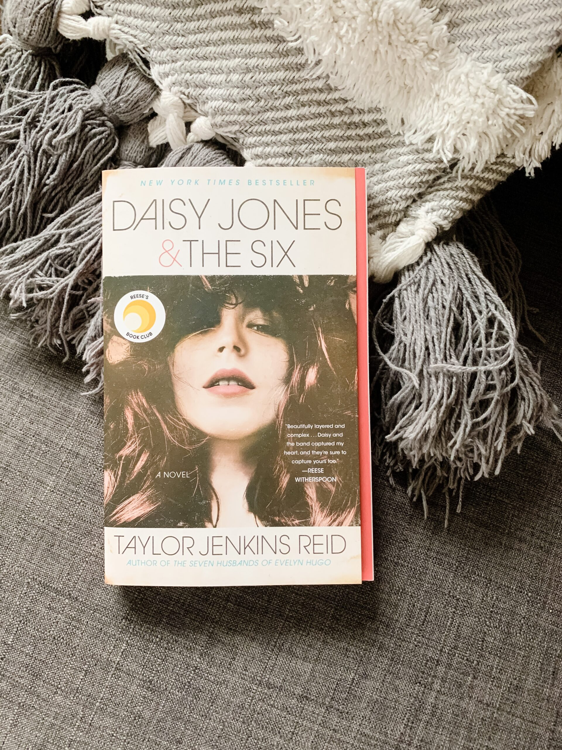 Image of the novel Daisy Jones and the Six, by Taylor Jenkins Reid. Book with image of rock star sits on a chair