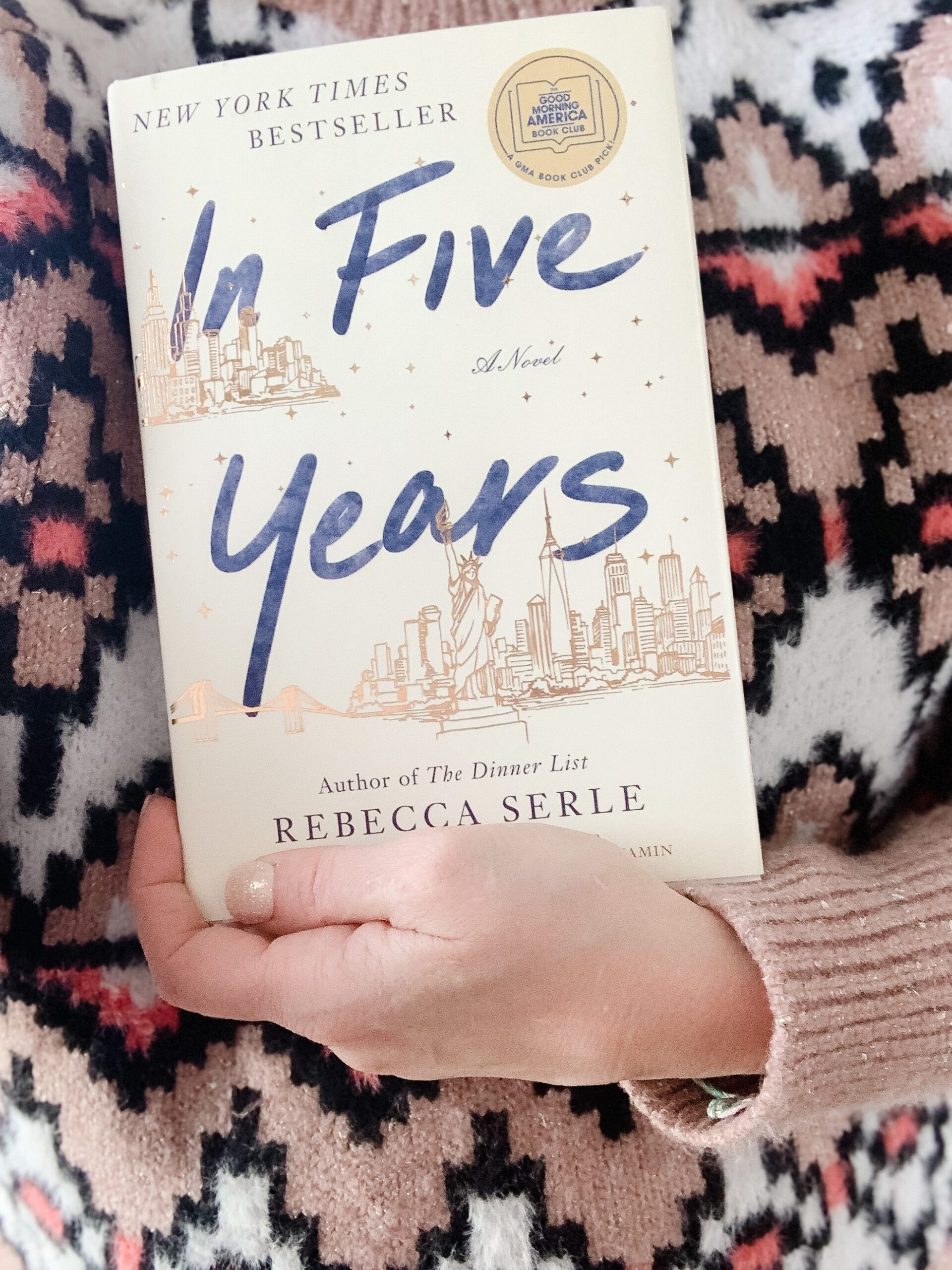 woman in fair isle sweater holding the novel In Five Years by Rebecca Serle. Book-A-Month Reading Challenge