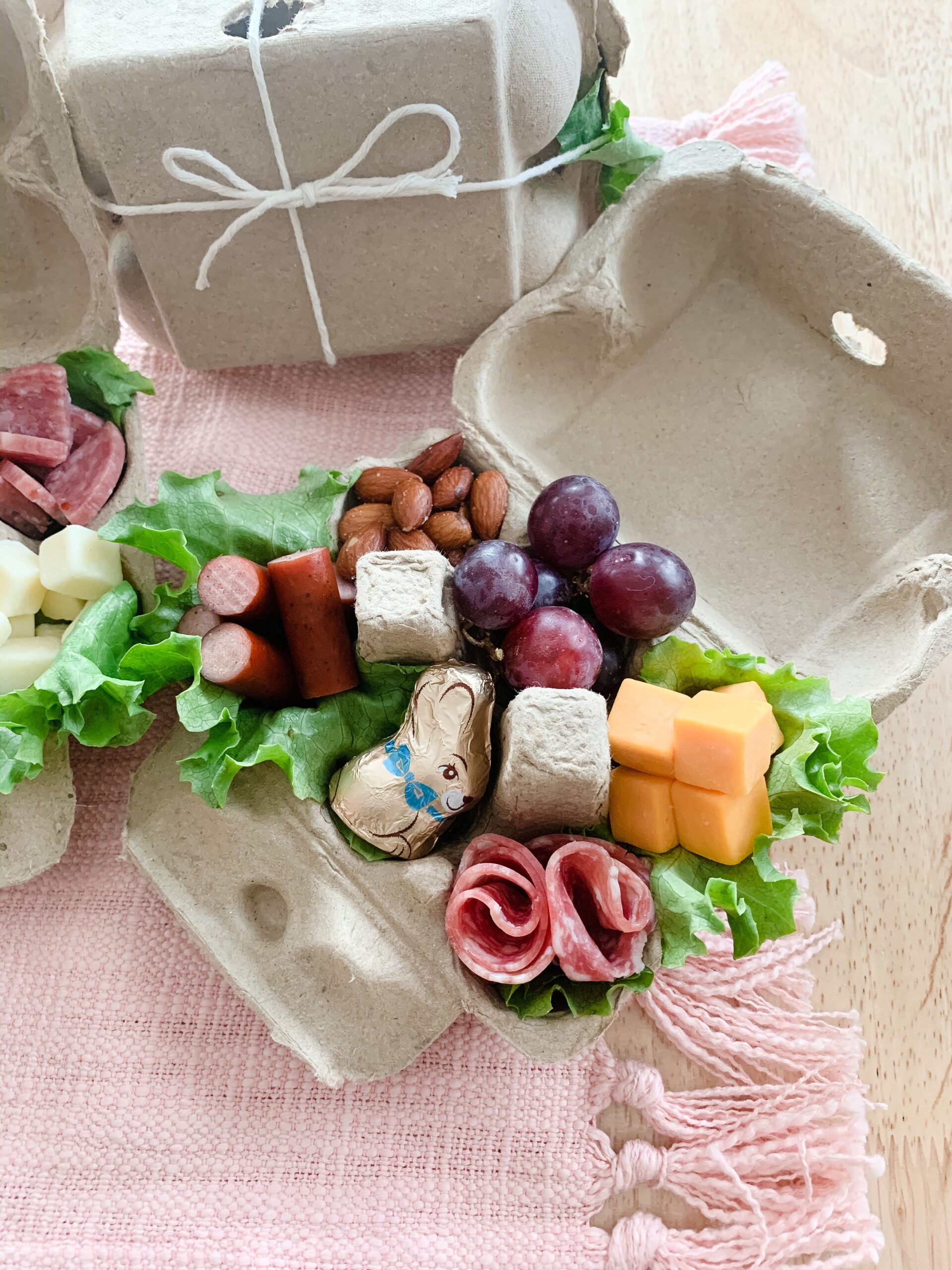assorted meats and cheeses in an egg carton charcuterie