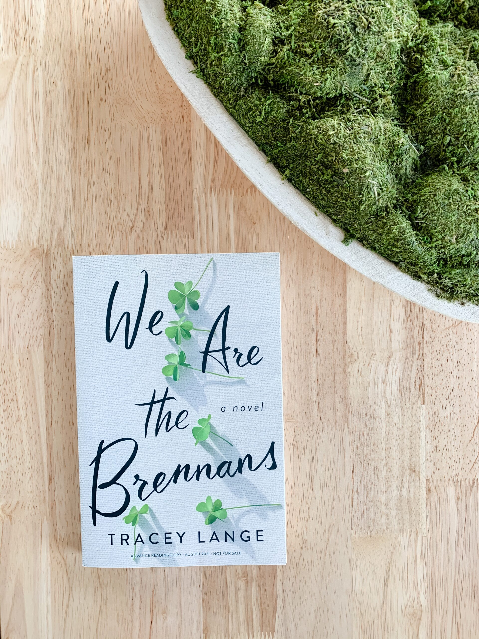 image of We Are the Brennans novel by Tracey Lange. Book is set on oak table with green moss.