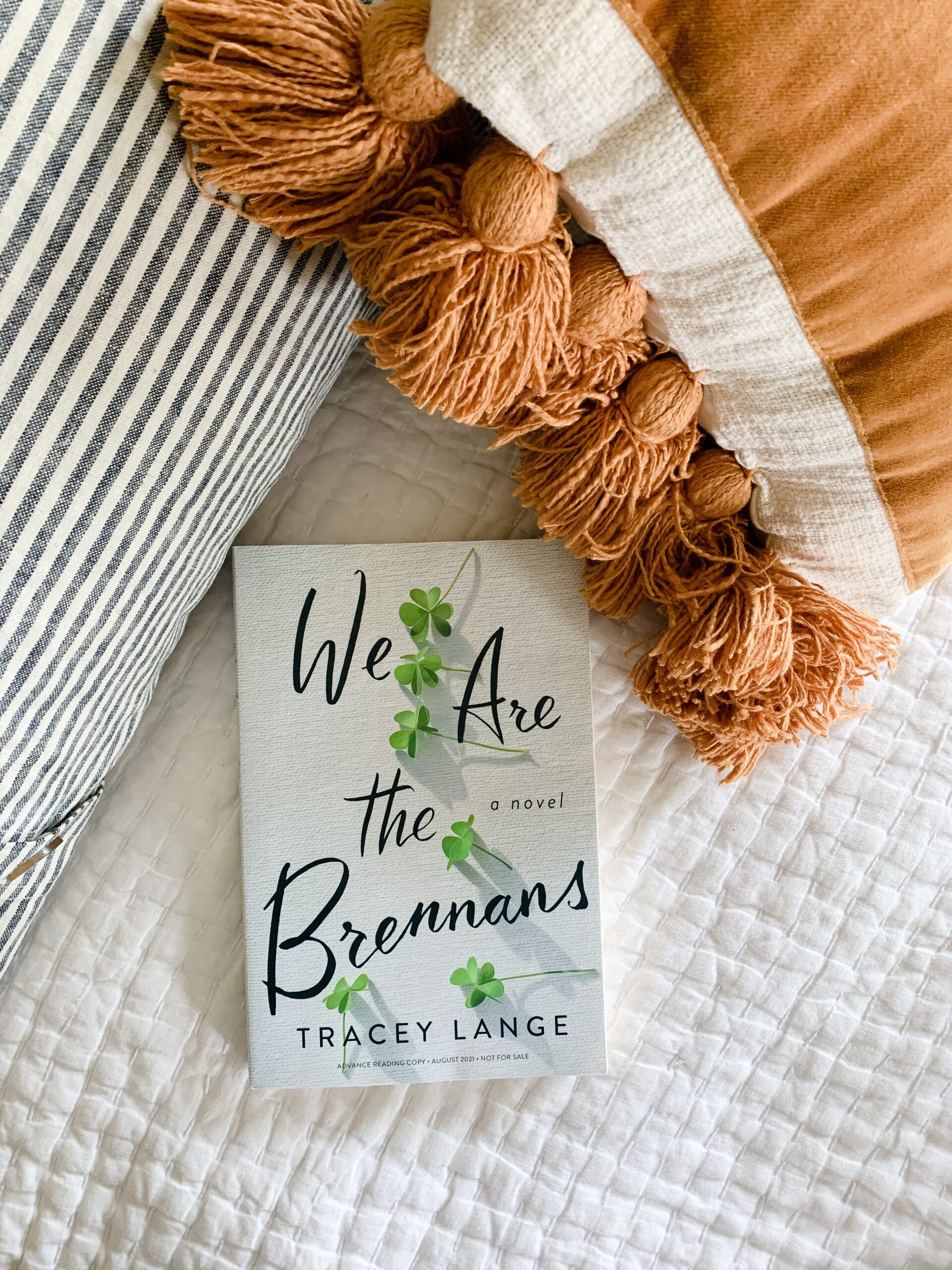 Image of We Are the Brennans novel by Tracey Lange on a bed surrounded by pillows.