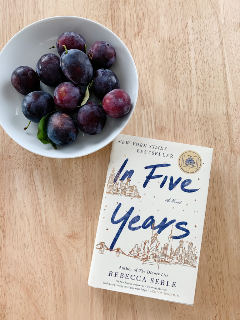 Novel In Five Years by Rebecca Serle on table next to plums